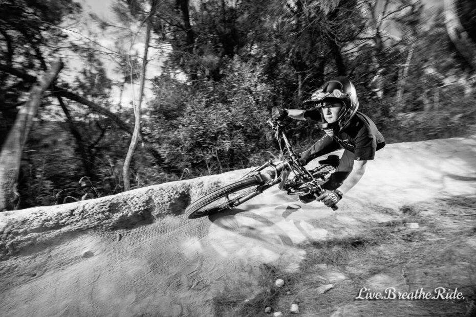 high fives - Zac Bradley riding MTB downhill in a berm