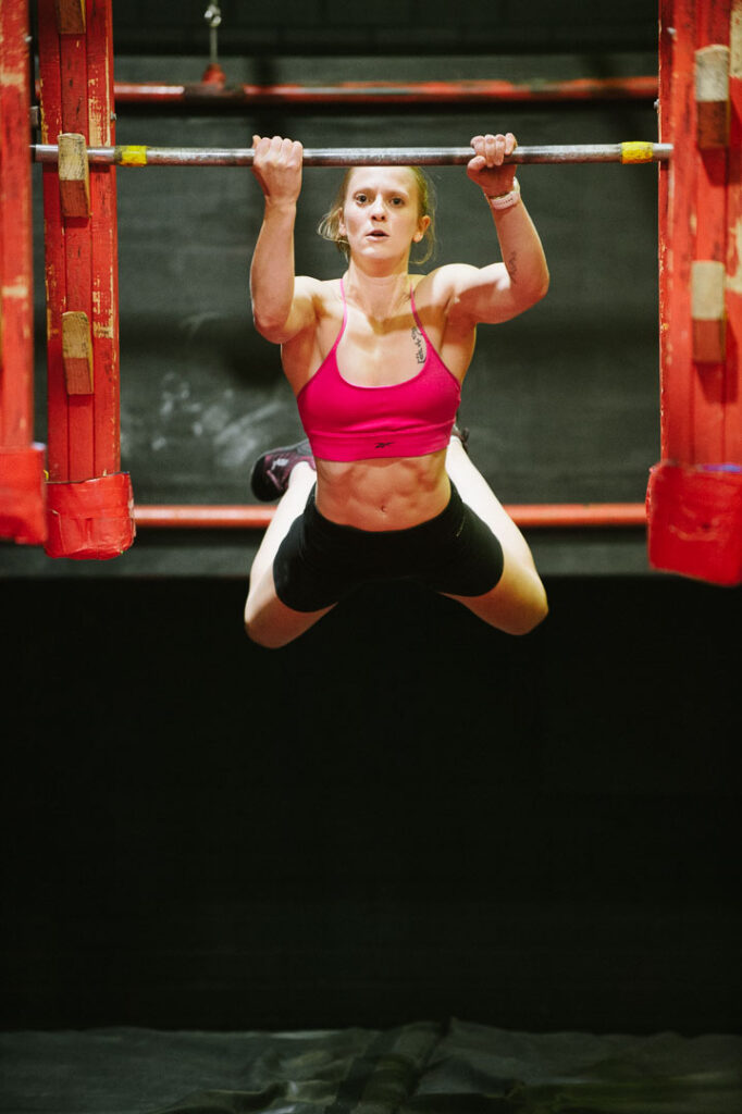 young female ninja warrior on the salmon ladder at Fighting Lyons Gym